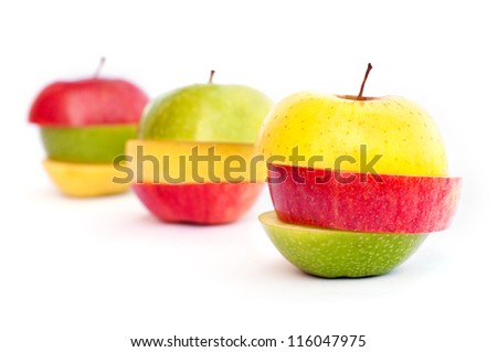 Three apples, green, red and yellow cut in slices - stock photo