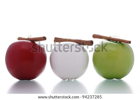 three apples with cinnamon sticks isolated on white background
