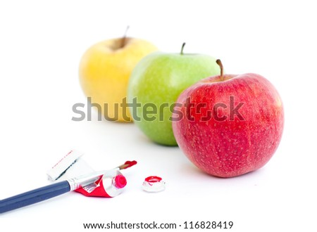 Three apples with paint and a brush