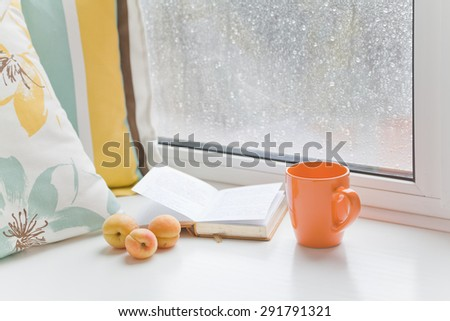 Three apricots on windowsill at the window with raindrops next to the book, pillow and cup on a rainy day. Set for a cozy summer reading. - stock photo