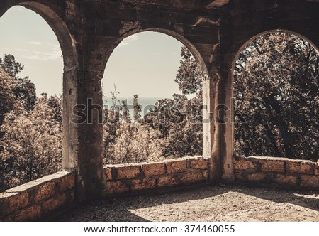 three arched windows with no glass in the unfinished house of limestone
