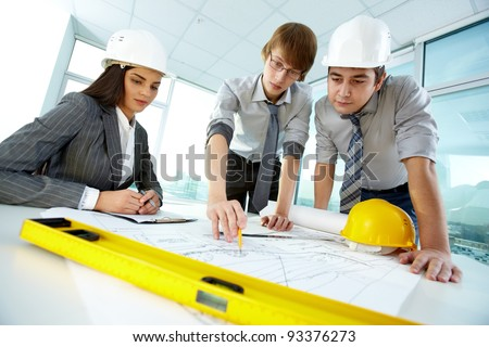 Three architects discussing new project in office - stock photo