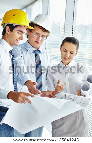 Three architects discussing sketch of new project - stock photo