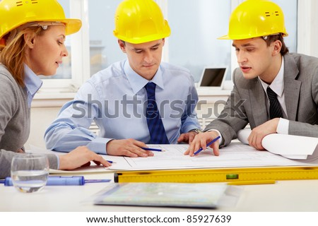 Three architects sitting at table and discussing paperwork