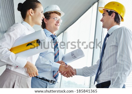 Three architects striking a deal in office - stock photo