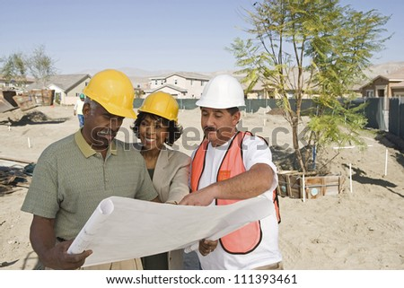 Three architects with blueprint discussing at construction site - stock photo