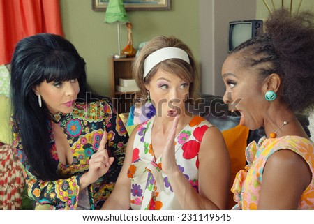 Three arguing female friends in 1960s style clothing - stock photo