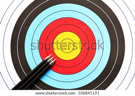 Three arrows aiming to the center of an archery target - stock photo