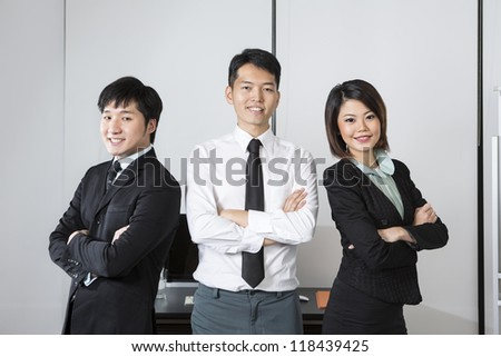 Three Asian Business colleagues standing in an office. - stock photo