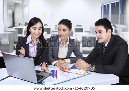 Three asian business team working with laptop at office - stock photo