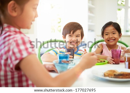 Three Asian Children Having Breakfast Together In Kitchen - stock photo