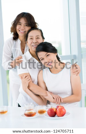 Three asian women standing behind the table