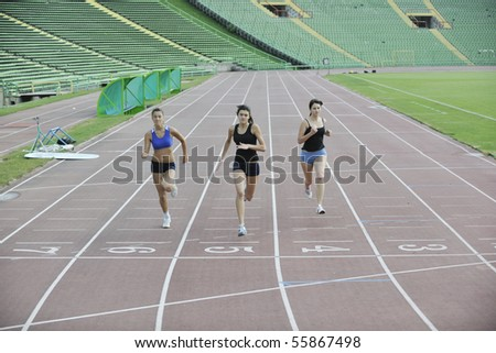 three athlete woman running on athletics race track on soccer stadium and representing competition concept in sport - stock photo