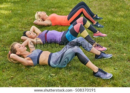 Three athletic women doing stomach workouts lying on a grass.