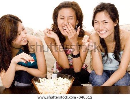 Three attractive asian women have fun eating popcorn - stock photo