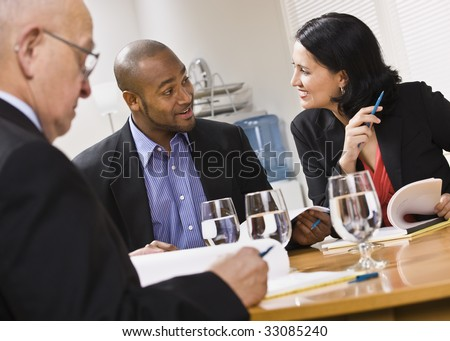 Three attractive business people sitting at a table with water and paperwork. Horizontal - stock photo