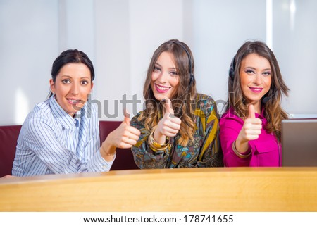 Three attractive business women showing thumbs up and smiling. - stock photo