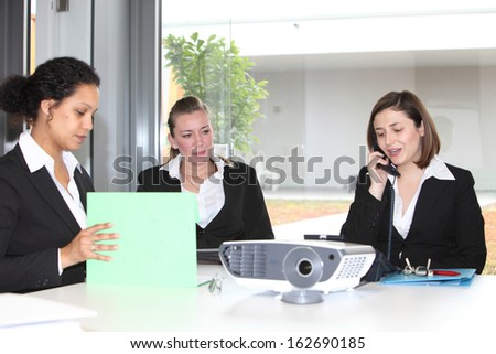 Three attractive businesswoman working together as a team sitting around a table with paperwork while one chats on the telephone - stock photo