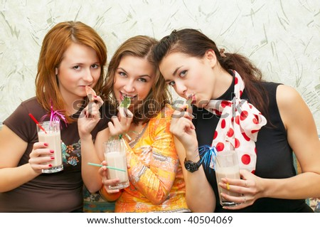 three attractive girl eating fruit candy and drink cocktails