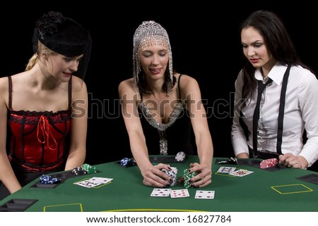 Three attractive girls dressed in moulin rouge clothing playing cards at green poker table - stock photo