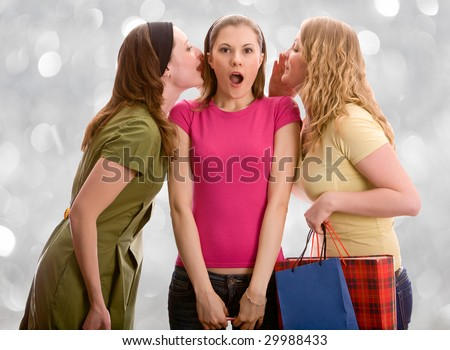Three attractive girls gossiping. Isolated on white - stock photo
