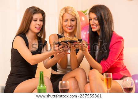 Three attractive girls in fancy dresses, sitting on a couch and smiling looking at birthday cake in their hands.