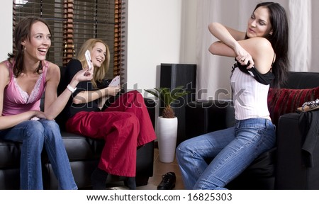 Three attractive girls playing strip poker at home - stock photo