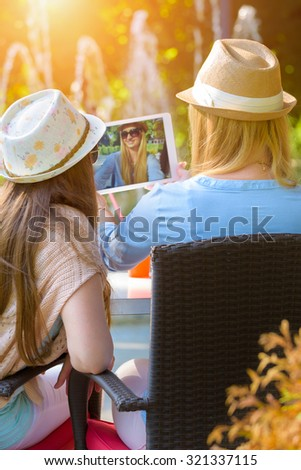 Three attractive hipster girls taking a selfie with digital tablet, back view