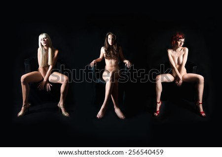 Three attractive nude models in front of dark studio background, their private parts are not visible - stock photo