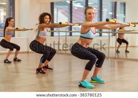Three attractive sport girls smiling, looking at camera, holding fitness stick and squatting while working out in fitness class - stock photo