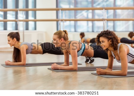 Three attractive sport girls smiling while doing plank exercise lying on yoga mat in fitness class - stock photo