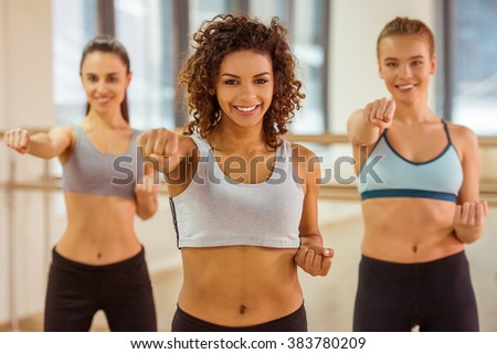 Three attractive sport girls smiling while working out and developing strength in fitness class - stock photo