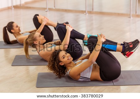 Three attractive sport girls smiling while working out lying on yoga mat in fitness class. Beautiful Afro-American girl looking at camera - stock photo