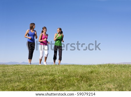 Three attractive women jogging outdoors together