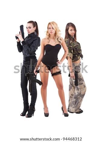 Three attractive young women handing guns. Studio shot. White background. - stock photo
