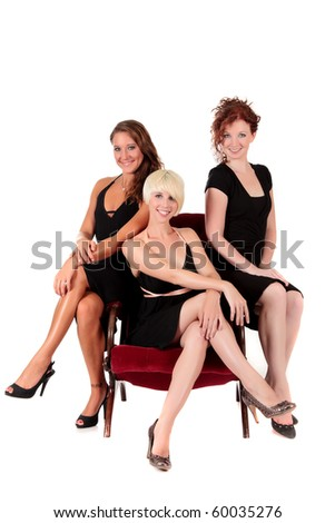 Three attractive young women in black sexy dresses sitting cross-legged on a armchair. Studio shot. White background.