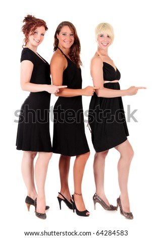 Three attractive young women in black sexy dresses with pointing hands. Studio shot. White background.