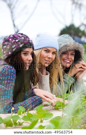 Three attractive young women lie on the beach together. They are all wearing hats to keep warm. Vertical shot. - stock photo