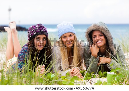 Three attractive young women lie on the beach together with the ocean in the background. Horizontal shot. - stock photo