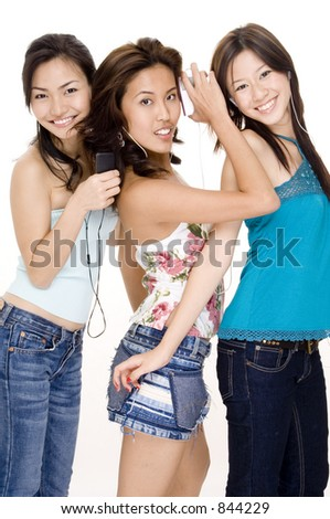 Three attractive young women listening to music on their mp3 players