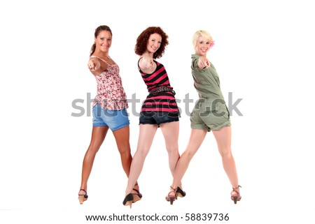 Three attractive young women smiling and pointing at camera. Studio shot. White background - stock photo