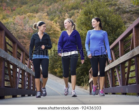 Three attractive young women talking a walking together - stock photo