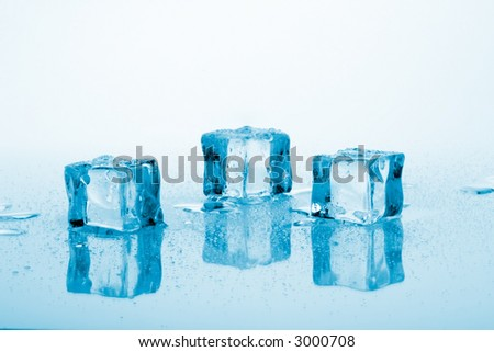 Three azure colored ice cubes melted in water on reflection surface ready to be added to a cocktail - stock photo