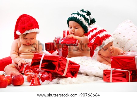 Three babies in xmas costumes playing with gifts - stock photo