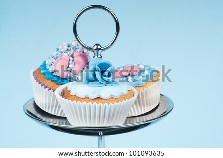 Three baby blue babyshower cupcakes on a stand - stock photo