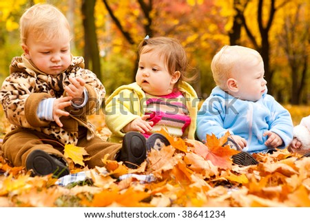Three baby friends sitting in autumn park