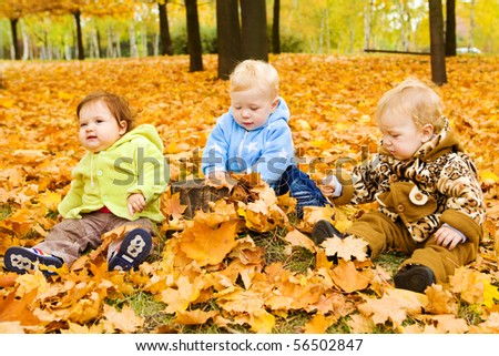 Three baby friends sitting on the yellow autumnal leaves - stock photo