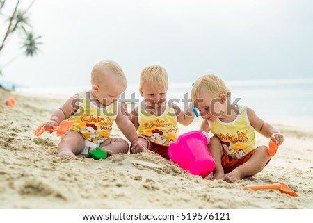 Three baby Toddler sitting on a tropical beach in Thailand and playing with sand toys. The yellow shirts chicken gang. Two boys and one girl