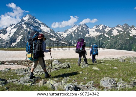 Three backpacker girls ,making there way in high mountains, travel background.
