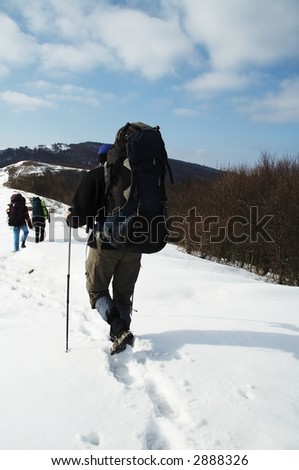 Three backpackers in winter hiking